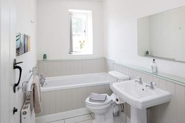 The bright family bathroom has a bath with shower attachment and a shower cubicle.
