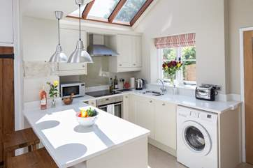 The very well-equipped kitchen has an induction hob, compact dishwasher and washing machine.