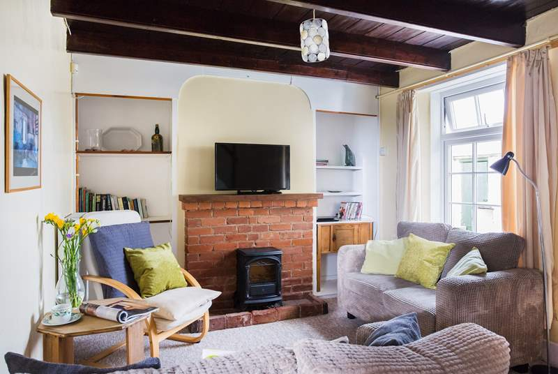 The sitting-room with feature brick fireplace and electric fire, the cottage also benefits from solar water heating and biomass central heating
