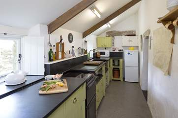The galley-style kitchen with slate sink and worktops.