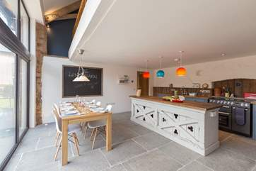The kitchen is designed for great fun as well as being very practical and fabulously equipped. Floor to ceiling windows look out over your front garden.