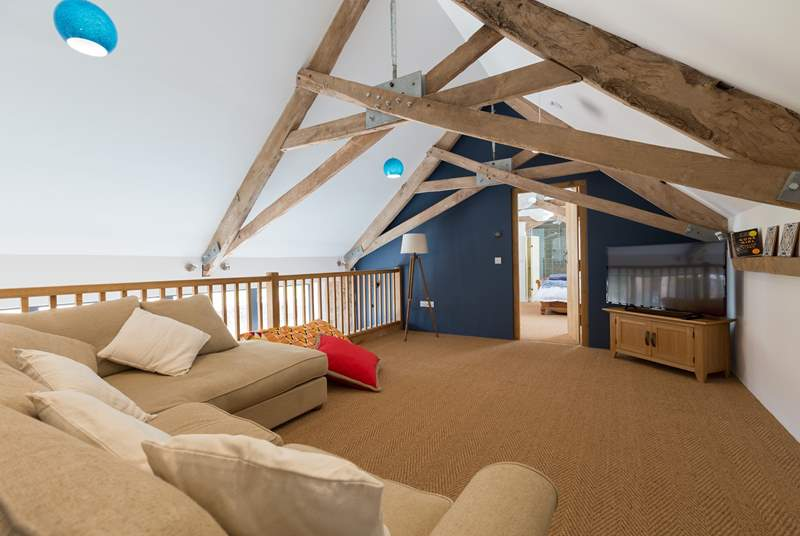 There is a mezzanine sitting-room where you can curl up to watch films. The door leads through to the magnificent double bedroom. The first floor beams are a great feature but are low where they meet.
