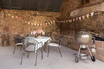 At the front of The Long  Barn, alongside the covered parking for guests, is this cheerful open fronted outside eating and barbecue-area.