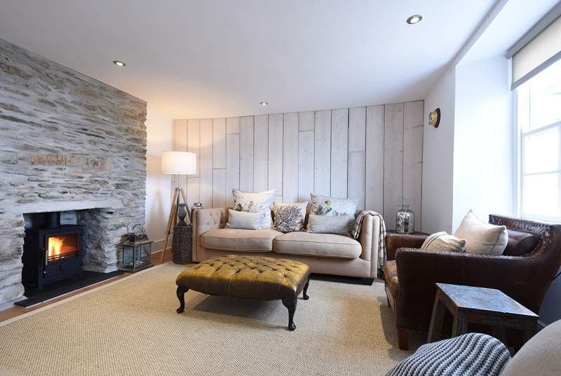 The lovely sitting-room has reclaimed wooden wall panelling and an original stone fireplace.