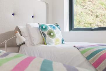 Crisp white linens on quality mattresses with just the right amount of colour.