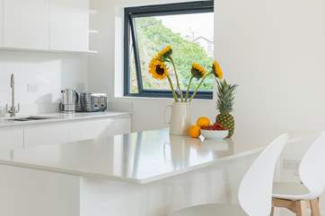 The sleek white marble topped kitchen units are not only practical but rather gorgeous too.