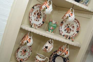 Vintage china hangs in the corner cupboard at Jinka's.