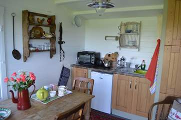 The kitchen and dining area of the cabin where modern facilities mix with lovely antique finds.