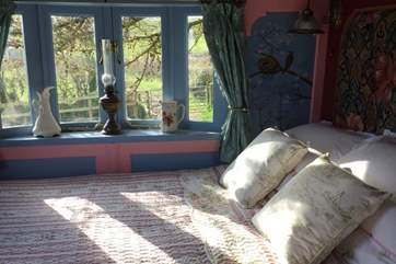 The sun streams through the window into the beautiful bedroom.