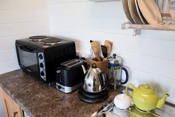 The kitchen area is well-equipped, including an electric cooker (mini oven and two-ring hob) and microwave.