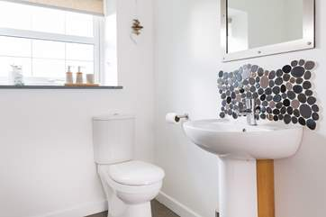 Little pebble tiles add a touch of seaside charm in the bathroom.