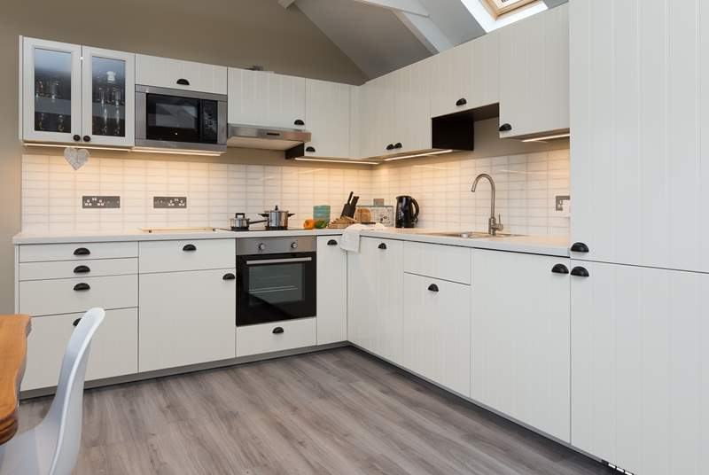 The kitchen offers plenty of work surface space yet does not impact on the feeling of space in the room.