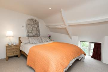 The king sized bed in the bedroom, with its characterful sloping ceilings - do take care if you are tall - and little window looking down to the garden.