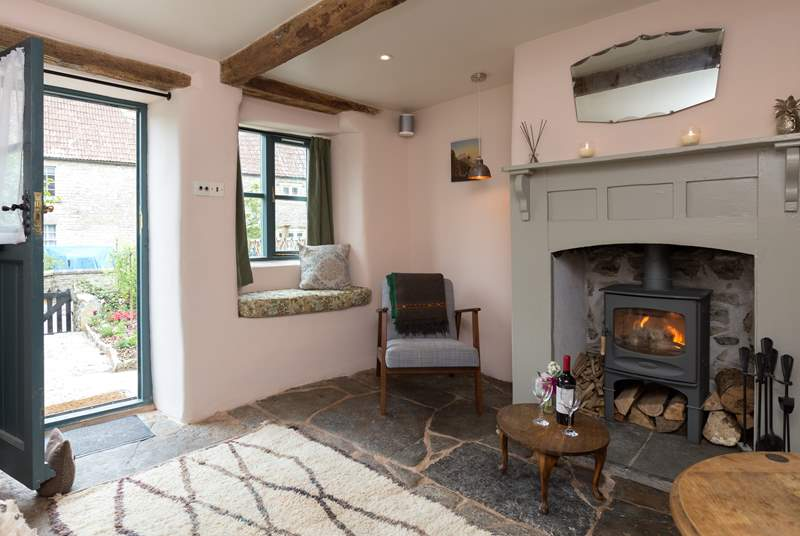 With original flagstone floors and a wood burning stove, the living room is such a welcoming room. There is a comfy sofa just out of this shot.