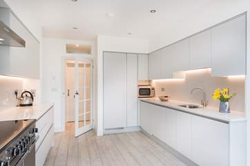 Smooth, pared back lines in the kitchen-area with handleless unit doors.