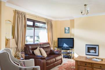 Comfortable chairs and sofas around the TV and wall-mounted electric fire.