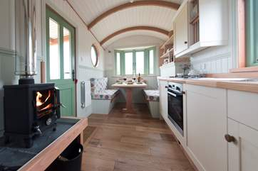 The light and airy wagon, looking past the kitchen  to the dining-area (the seats fold down with ease to become the second double bed).