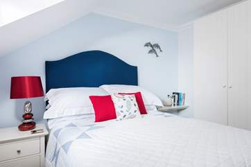 Soft furnishings with a splash of red and blue bring a freshness to this comfortable bedroom.