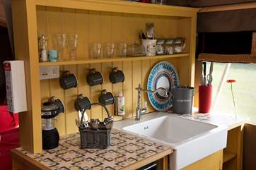 The kitchen area is well-equipped for your glamping needs.