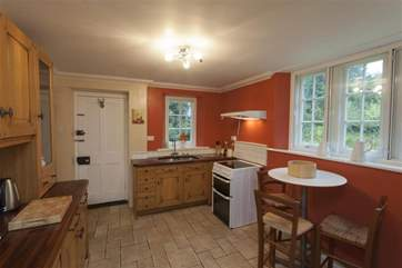 The kitchen has a door to the gardens.
