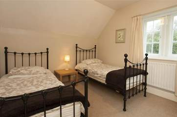 The twin room features cast iron bedsteads and overlooks the gardens.