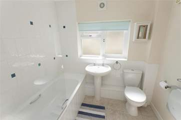 The clean white bathroom suite.