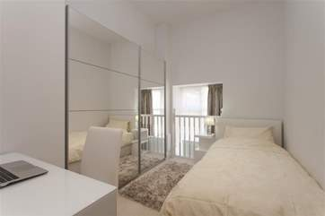 The single bedroom has a quirky window and balustrade.