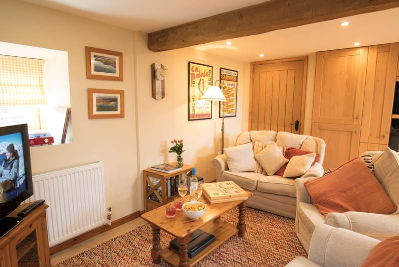 The cosy sitting area is part of an open-plan space, with a large kitchne and dining area.