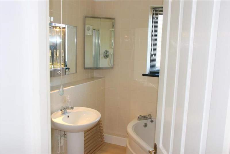 The en suite bathroom with corner bath and shower overhead.