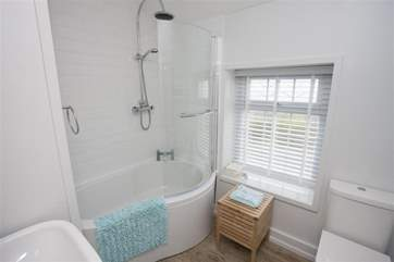 The modern white bathroom suite has a power shower.
