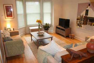 The living area is spacious and has soft tones.