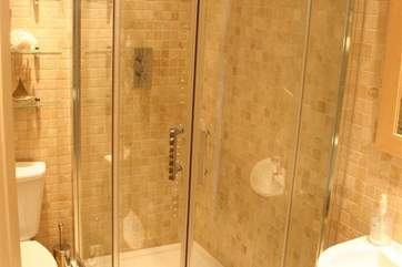 The shower room is fully tiled with a large shower cubicle.