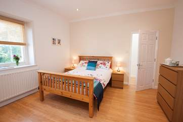 The master bedroom has plenty of space and is simply decorated, making it feel calm and relaxing