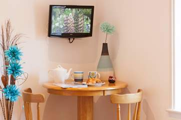 In the master bedroom is a small TV, bar stools and table to enjoy your morning coffee and read your daily newspaper