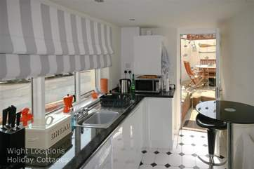 The galley kitchen leads through to the dining-area, inside or out for those lazy summer days.