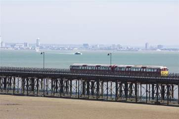 Watch the island train trundle it's way up the Victorian pier to collect and drop off passengers for the catamaran