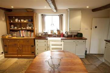 The country style kitchen is open plan with the dining area