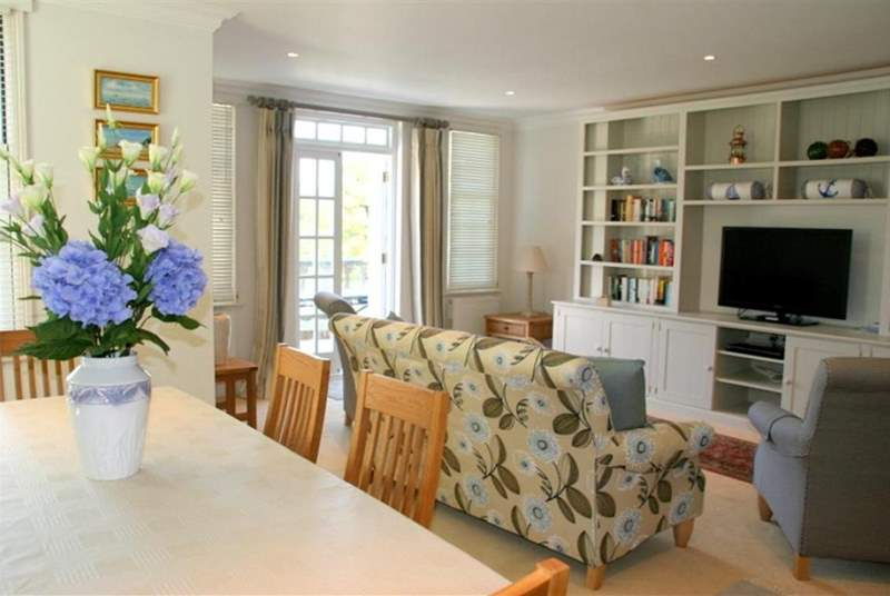 The open plan living room and dining room has plenty of space and doors that open out onto a terrace that overlooks the pool