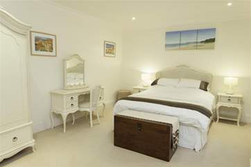 The master bedroom has a king size bed and an ensuite bathroom with walk in shower
