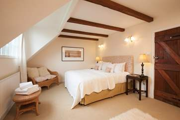 The beautiful master bedroom beautifully complete with wooden beams on the ceiling for that country cottage feel