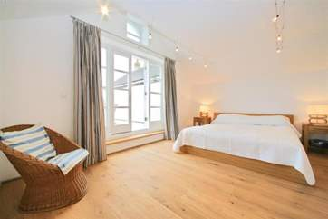 The master bedroom is in the modern extension of Creekside with doors out to a decked terrace