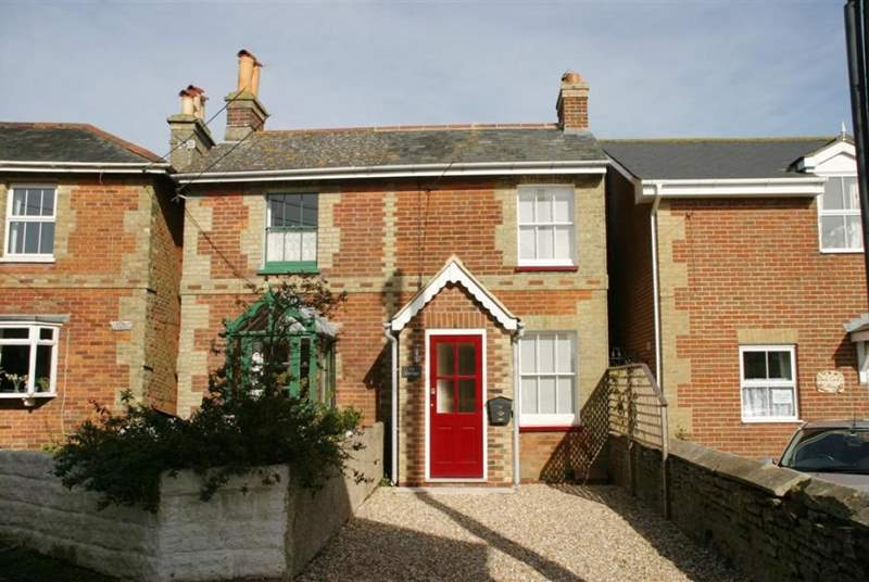 The semi-detached property has a red door.