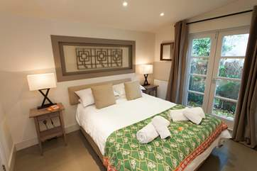 The master bedroom is a sanctuary decorated for ultimate relaxation, with patio doors to let in the warm summer breeze