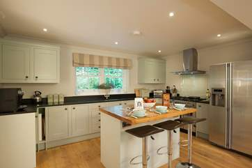 The sytlish kitchen with island and breakfast bar is an ideal space to prepare your favourite meals.