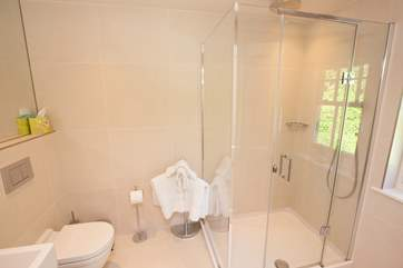 The en suite off the second double bedroom with spacious shower and a light and modern decor.