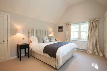 The impressive master bedroom has views out to the front garden.