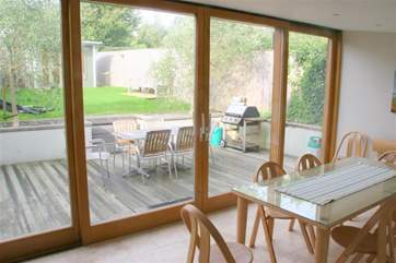 Open plan kitchen and dining room with large sliding doors to the patio and enclosed garden