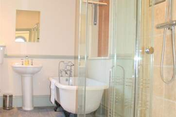 Family bathroom with walk-in shower and claw foot bathtub with shower over the bath