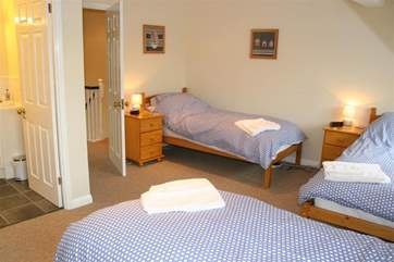 The family bedroom is spacious with three single beds.