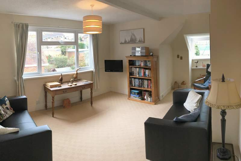 The sunny living room has views of the neighbouring sports club tennis courts